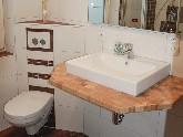 Eine Arbeitsplatte als Auflage für das Waschbecken bietet zusätzliche Ablagefläche