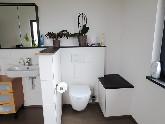 WC-Nische mit zusätzlicher Sitzmöglichkeit, worin ein Wäscheabwurfschacht integriert wurde